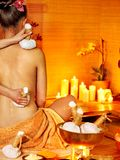 Woman getting thai herbal massage ball. Royalty Free Stock Photo