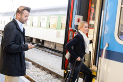 Woman getting on train man texting phone. Woman getting on train men texting phone commuters journey stairs Stock Photography