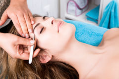 Woman getting tweezing eyebrow Stock Photos