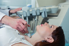 Woman getting ultrasound of a thyroid from doctor.  stock photos