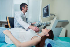 Woman getting ultrasound of a thyroid from doctor.  royalty free stock photography