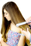 Woman getting very long blond hair straightened by hairstylist isolated Royalty Free Stock Photography