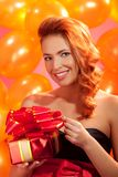 Woman with gift. Portrait of happy woman with gift box over pink background Stock Photo