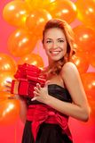 Woman with gift. Portrait of happy woman with gift box over pink background Royalty Free Stock Photo