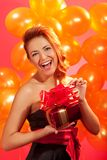 Woman with gift. Portrait of happy woman opening gift box over pink background Royalty Free Stock Photo