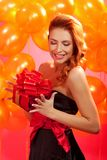 Woman with gift. Portrait of happy woman opening gift box over pink background Royalty Free Stock Photography