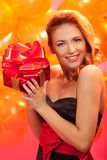 Woman with gift. Portrait of happy woman trying to guess what is in the gift box over pink background Royalty Free Stock Photo