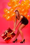 Woman with gift. Portrait of happy woman dragging gift box over pink background Royalty Free Stock Image