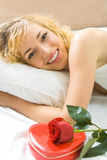 Woman with gift on the bed Stock Photography