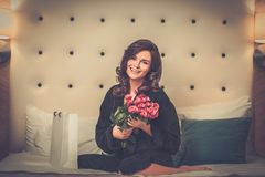 Woman with gift on a bed in hotel room Royalty Free Stock Photography