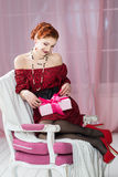Woman with gift box on chair. Christmas, New Year eve Stock Image