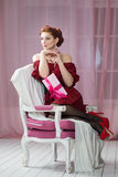 Woman with gift box on chair. Christmas, New Year eve Royalty Free Stock Photo