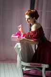 Woman with gift box on chair. Christmas, New Year eve Royalty Free Stock Photography