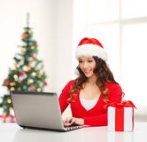 Woman with gift box and laptop computer Stock Image