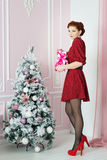 Woman with gift box near fir tree. Christmas, New Year eve Royalty Free Stock Photos