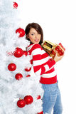 Woman with gift box next to christmas tree Royalty Free Stock Photography