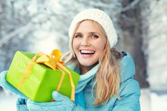 Woman with gift box. Pretty woman with a gift box in her hands. christmas winter outdoors Stock Photography
