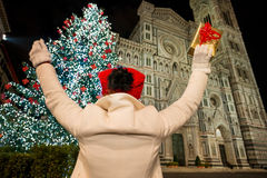 Woman with gift box rejoicing near Christmas tree in Florence. Woman in white coat with gift box rejoicing in front of Christmas tree near Duomo in the evening stock image