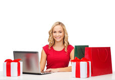 Woman with gift boxes, bags and laptop computer Stock Photos