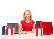 Woman with gift boxes, bags and laptop computer Stock Photography