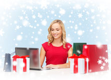 Woman with gift boxes, bags and laptop computer Royalty Free Stock Photo