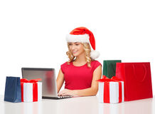 Woman with gift boxes, bags and laptop computer Royalty Free Stock Image