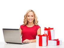 Woman with gift boxes and laptop computer Royalty Free Stock Photo