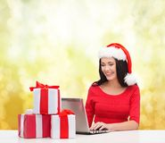 Woman with gift boxes and laptop computer Royalty Free Stock Photos