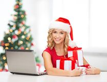 Woman with gift boxes and laptop computer Royalty Free Stock Photography