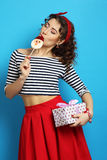 Woman with a gift and candy.  Pin up style. Royalty Free Stock Images