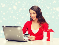 Woman with gift, laptop computer and credit card Stock Image