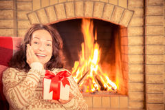 Woman with gift near fireplace Royalty Free Stock Photos