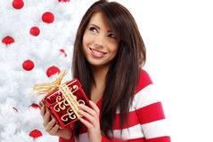 Woman with gift  next to white christmas tree Stock Photo