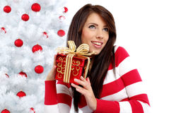 Woman with gift  next to white christmas tree Stock Image