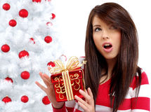 Woman with gift  next to white christmas tree Royalty Free Stock Photo