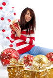 Woman with gift  next to white christmas tree Stock Images