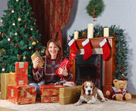 Woman with gift in the room with fireplace and Christmas decorat Stock Images