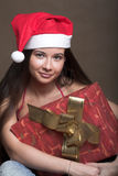 Woman with a gift in Santa-hat Royalty Free Stock Images