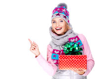 Woman with a gift in a winter outerwear  pointing by finger Stock Images