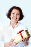 Woman with giftbox. Portrait of middle-aged female with golden giftbox looking at camera stock images