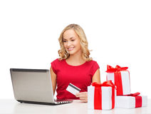 Woman with gifts, laptop computer and credit card Royalty Free Stock Images