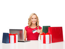 Woman with gifts, laptop computer and credit card Stock Photos