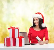 Woman with gifts, laptop computer and credit card Royalty Free Stock Photo
