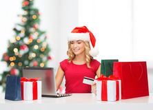 Woman with gifts, laptop computer and credit card Royalty Free Stock Photography
