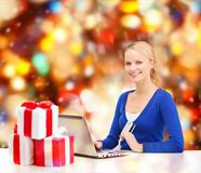 Woman with gifts, laptop computer and credit card Stock Images