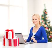 Woman with gifts, laptop computer and credit card Royalty Free Stock Photos