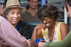 Woman Giggling with Friends. Diverse group of giggling men and women in coffee house Stock Photo