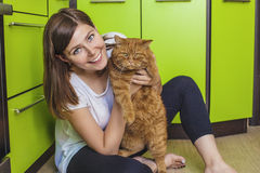 Woman with a ginger cat in her arms cuddling on the kitchen. The woman with a ginger cat in her arms cuddling on the bright kitchen Stock Photography