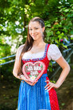 Woman with gingerbread hart in Bavaria beergarden. Young woman in traditional Bavarian clothes or tracht with a gingerbread souvenir heart in beergarden on Stock Photos