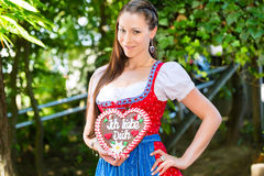 Woman with gingerbread hart in Bavaria beergarden. Young woman in traditional Bavarian clothes or tracht with a gingerbread souvenir heart in beergarden on Stock Photo